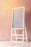 空的黑板画架,在砖背景的立场 免版税库存照片