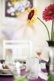 空的玻璃、蛋糕和花花束在桌上的 免版税库存图片