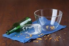 空的玻璃和瓶与芯片面包屑的啤酒  库存照片