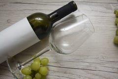 空的玻璃和绿色葡萄 库存图片