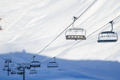 空的滑雪电缆车,缆绳椅子在滑雪胜地的一个晴天 免版税库存图片
