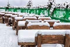 空置多雪的木咖啡馆桌透视行在冬天 免版税库存图片