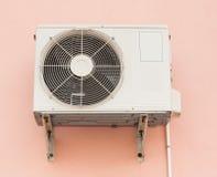 空调器在橙色墙壁上的压缩机单位 库存图片