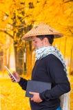 穿一个亚洲圆锥形帽子和围巾的一个英俊的西班牙年轻企业人的画象在他的举行他的脖子上 免版税库存图片
