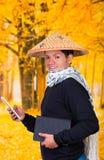 穿一个亚洲圆锥形帽子和围巾的一个英俊的西班牙年轻企业人的画象在他的举行他的脖子上 免版税库存照片