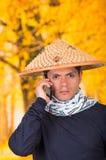 穿一个亚洲圆锥形帽子和围巾的一个英俊的西班牙年轻企业人的画象在他的脖子上使用他的 免版税库存图片