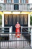 穿一个典型的中国新娘的丝绸红色礼服的中国妇女,装饰用金黄菲尼斯和扯拽在桥梁 免版税库存图片