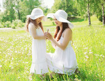 穿一个草帽用蒲公英的愉快的母亲和小女孩孩子 免版税库存图片