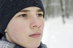 穿一个蓝色帽子和一条蓝色方格的围巾的少年男孩的画象 免版税图库摄影