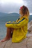 穿一个黄色雨衣的一个性感的时装模特儿户外 免版税库存图片