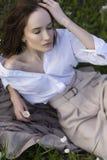 穿一件时髦白色衬衣的美丽的时髦的女孩,米黄 库存照片