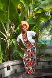 穿一件明亮的五颜六色的全国礼服的一名快乐的非裔美国人的妇女的垂直的充分的身体在庭院里摆在 库存照片