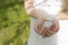 穿一件白色礼服的一个十几岁的女孩的手小心地是 免版税图库摄影