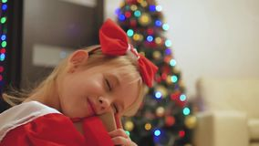 穿一件红色礼服的儿童女孩打开Xmas出席 有圣诞节礼物盒的愉快的矮小的微笑的女孩 舒适温暖 股票录像
