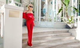穿一件红色礼服的美丽的现象惊人的典雅的豪华性感的白肤金发的式样妇女,审阅购物的街道  库存图片