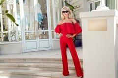 穿一件红色礼服的美丽的现象惊人的典雅的豪华性感的白肤金发的式样妇女,审阅购物的街道  免版税库存图片