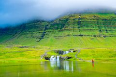 穿一件红色衬衣的妇女在水中趟过了对Kirkjufellsfoss 库存图片