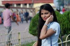穿一件蓝色西部礼服的印度女孩画象和在手中观看 库存照片