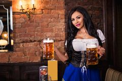 穿一套传统巴法力亚礼服少女装的慕尼黑啤酒节妇女摆在与啤酒杯在酒吧 免版税库存照片