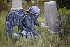 穿一套天使服装的女孩在一个老严重围场 免版税库存图片