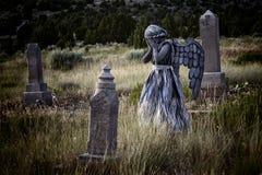 穿一套天使服装的女孩在一个老严重围场 库存图片