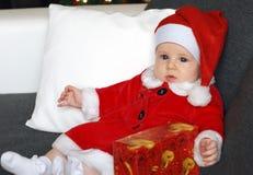 穿一套逗人喜爱的圣诞老人服装的小女婴 免版税图库摄影