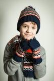 穿一条羊毛帽子和围巾的愉快的孩子 免版税库存照片