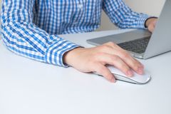 穿一蓝色格子衬衫的一个人的特写镜头图象使用拿着老鼠的手在办公室 免版税库存照片