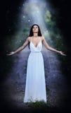 穿一件典雅的长的白色礼服的可爱的小姐享受神圣光射线在她的面孔的在被迷惑的森林 长的h 库存照片