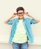 穿一件方格的衬衣的玻璃的愉快的微笑的聪明的少年男孩 免版税库存照片