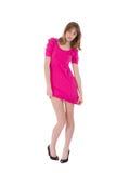穿一件桃红色礼服的美丽的年轻害羞的妇女 免版税库存图片
