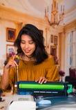 穿一件棕色女衬衫的美丽的妇女固定复印机在维护期间使用螺丝刀 免版税库存图片