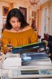 穿一件棕色女衬衫的美丽的妇女固定复印机在维护期间使用螺丝刀 库存图片