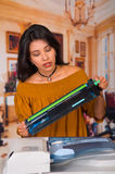 穿一件棕色女衬衫的美丽的妇女固定复印机在维护期间 库存照片