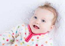 穿一件温暖的冬天夹克的逗人喜爱的微笑的女婴 免版税图库摄影