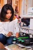 穿一件白色女衬衫,蹲下和修理复印机和微笑在维护期间的美丽的妇女使用a 库存照片