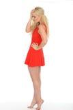 穿一件短的红色套衫连超短裙的可爱的性感的体贴的年轻白肤金发的妇女 库存图片