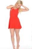 穿一件短的红色套衫连超短裙的可爱的性感的嬉戏的年轻白肤金发的妇女 库存照片