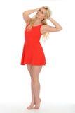 穿一件短的红色套衫连超短裙的可爱的性感的调情的年轻白肤金发的妇女 库存图片