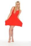 穿一件短的红色套衫连超短裙的可爱的性感的逗人喜爱的年轻白肤金发的妇女 库存图片