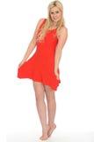 穿一件短的红色套衫连超短裙的可爱的性感的逗人喜爱的年轻白肤金发的妇女 图库摄影
