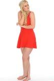 穿一件短的红色套衫连超短裙的可爱的性感的逗人喜爱的年轻白肤金发的妇女 免版税图库摄影
