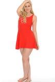 穿一件短的红色套衫连超短裙的可爱的性感的逗人喜爱的年轻白肤金发的妇女 库存照片
