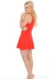 穿一件短的红色套衫连超短裙的可爱的性感的逗人喜爱的年轻白肤金发的头发的妇女 库存照片