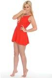 穿一件短的红色套衫连超短裙的可爱的性感的震惊年轻白肤金发的妇女 免版税库存图片