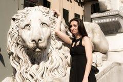 穿一件黑礼服的美丽的女孩在哥特式样式狮子雕象旁边 免版税库存图片