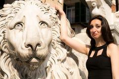 穿一件黑礼服的美丽的女孩在哥特式样式狮子雕象旁边 图库摄影