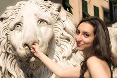 穿一件黑礼服的美丽的女孩在采摘他的鼻子的哥特式样式狮子雕象旁边 免版税库存照片