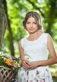 穿一件精密白色礼服的美丽的女孩获得乐趣在有充分运载一个美丽的篮子花的自行车的公园 葡萄酒 免版税库存照片