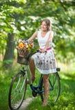 穿一件精密白色礼服的美丽的女孩获得乐趣在有自行车的公园 健康室外生活方式概念 葡萄酒风景 免版税库存照片